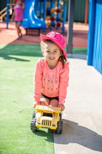 young girl in pink cat jumper playing with a yellow truck