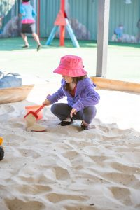 young girl in a pink hat playing with a toy shovel in a sandpit